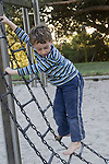 Berkeley CA Boy, five, climbing on chain structure at playground  MR