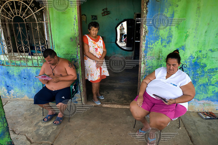 A family sit and read magazines outside their home in Ciudad Ojeda. They are waiting to be relocated to a new home as subsidence caused by oil exploration has damaged their current premises.....