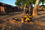 Jessie Chiumia grinds peanuts in Kaluhoro, Malawi. With support from the Ekwendeni Hospital AIDS Program, she and other villagers participate in a Building Sustainable Livelihoods program, working together to earn and save money, raise more nutritious food, and receive vocational training.