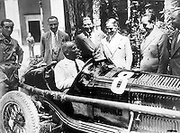 Benito Mussolini driving an Alfa Romeo racing car. In the center Prospero Gianferrari. circa 1931.