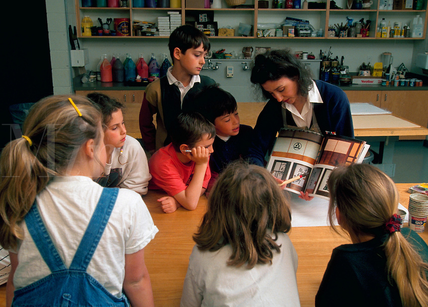 A teacher instructs elementary students in an school classroom.