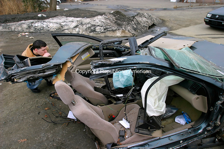 WOLCOTT, CT--01 APRIL 2007--040107JS02- Kenny Pelton of Wolcott looks over a car Honda Prelude that was involved in an accident on Beecher Road in Wolcott on Saturday night. The car was split in to from the impact. Pelton said he knows the two boys involved in the crash.<br /> Jim Shannon / Republican-American