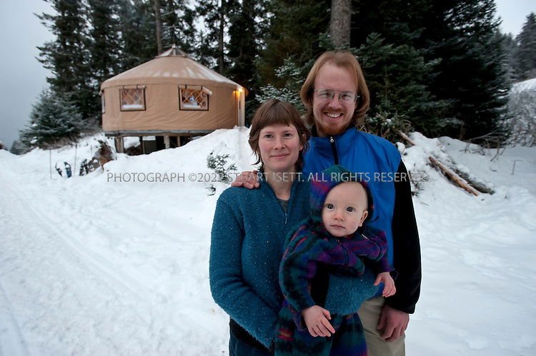 12/11/2009--Seldovia, Alaska, USA..Bretwood Higman, Erin McKittrick and their son Katmai, in front of their yurt in Seldovia, Alaska...The yurt is made by Nomad Shelter in Homer, Alaska, and cost about $14,000.  Bretwood Higman ('Hig'), 33 and Erin McKittrick, 30, built it in November, 2008 on land owned by Hig's mother in Seldovia. The yurt is 24' in diameter, the ceiling is over 12' in the middle, 7' around the edge. It has no running water but does have electricity and internet access...McKittrick grew up in Seattle and met Higman, from Seldovia, at Carleton College in 2001.  In June 2007, the couple left Seattle for the Aleutian Islands, traveling 4000 miles solely by human power through some of the most rugged terrain in the world; their adventure has recently been published in a book written by McKittrick with Hig's photographs titled, 'A Long Trek Home: 4,000 Miles by Boot, Raft, and Ski'...Together, the couple also run a small environmental non-profit, Ground Truth Trekking, which uses trekking to explore the complexities of natural resource issues.  The couple lives with their 10 month old son son, Katmai, in Seldovia, Alaska, a 300 person village just off the end of the road system...©2009 Stuart Isett. All rights reserved.