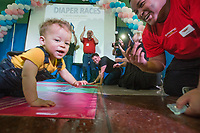 NWA Democrat-Gazette/BEN GOFF @NWABENGOFF<br /> Grayson Smith, 10 months, crawls to his father Ladarius Smith of Forest City to win his heat in the 'Diaper Races' Saturday, March 10, 2018, during the Power 105.7 Worlds Largest Baby Shower at the Jones Center in Springdale. The event sponsored by Washington Regional, with proceeds from ticket sales going to March of Dimes, included a variety of vendors, activities and seminars to help new and expecting parents provide the best care for their babies.
