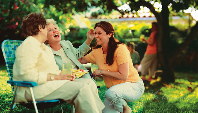 Three women sit in a botanical garden and laugh together