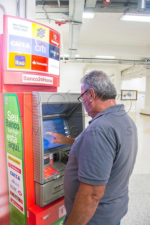 Homem sacando dinheiro, Aparecida - SP, 10/2016. Uso de imagem autorizado.