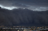 Apr. 26, 2011; Phoenix, AZ, USA; A dust storm converges on downtown Phoenix airplane airliner plane jet haboob sandstorm dust monsoon storm chaser chasing city dusk Arizona