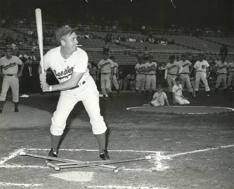 UNITED STATES - 1966: Silvio O. Conte, R-Mass., with a cigar clamped in his teeth and his recently discarded crutches below him, lines up to take a Democrat team pitch at the 1966 Congressional Baseball game.  (Mickey Senko/CQ Roll Call File Photo)