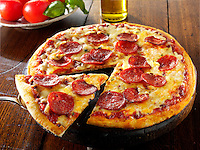 Pizza topped with pepperoni & cheese  with a slice out photo. Funky Stock pizzas photos