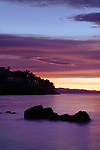Beautiful pink sunset scenery on the ocean coast with lights of residential houses on dark rocky shores in Nanaimo, Vancouver Island, BC, Canada.