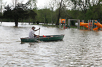 Joshua Robertson paddles his boat past a playground near the intersection of North Main Street and Second Street in the Red Star District of Cape Girardeau, MO, on Thursday, April 28, 2011.