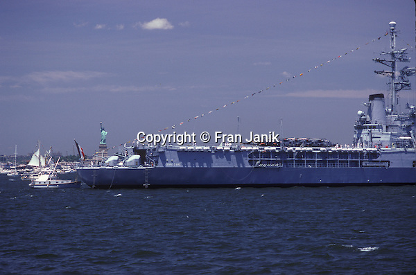 "The French war ship ""Jeanne De Arc""seen from the stern sits at anchor in New York Harbor. The ship is seen during  the celebration for the Statue of Liberty, on July 5th in 1986. The statue surrounded by other vessels , is seen in the backround."