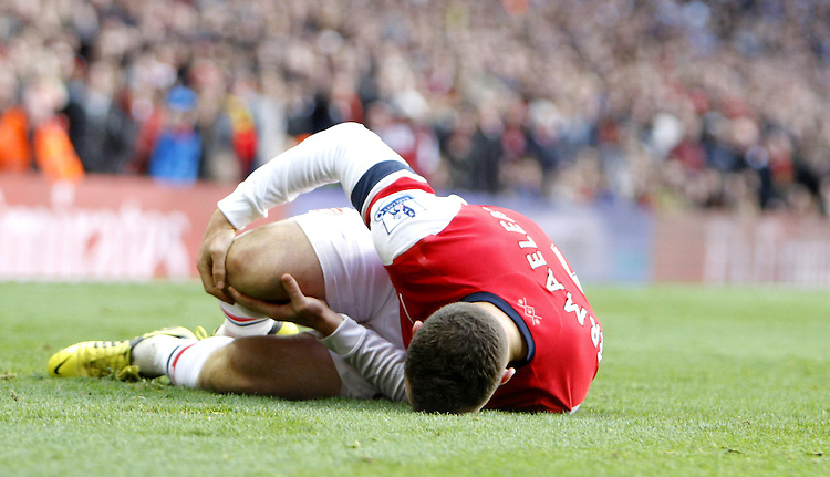 Arsenal's Thomas Vermaelen is injured by Queens Park Rangers' Stephane Mbia who then receives a red card sending off..Football - Barclays Premiership - Arsenal v Queens Park Rangers - Sturday 27th October 2012 - Emirates Stadium - London..