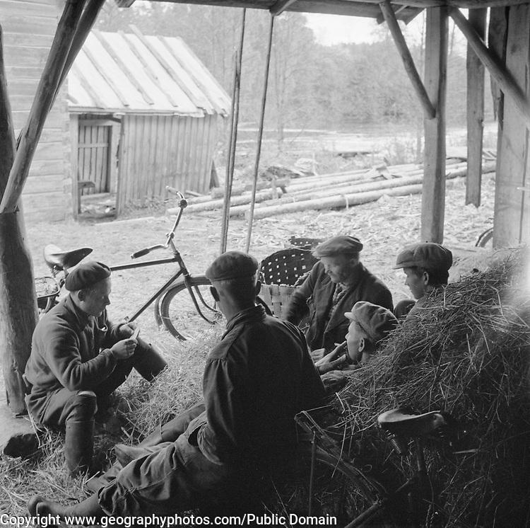 Male farm workers having a break in a  barn, Finland 1955
