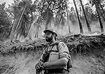 September 8, 1987 Yosemite National Park, California -- Stanislaus Complex Fire -- Firefighter stands watch on fire burning above Harden Flat near Yosemite. The Stanislaus Complex Fire consumed 28 structures and 145,980 acres.  One US Forest Service firefighter David Ross Erickson died from a tree falling accident.