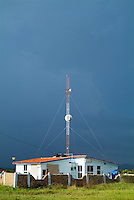 Country house with a large telecommunication antenna against a stormy sky, Cuba.
