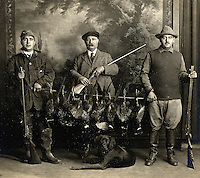 Vintage photograph of 3 hunters posing with their guns and dog.