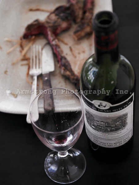 An opened bottle of red wine with empty wine glass in foreground, plate with eaten t-bone steak, fork, knife in background.
