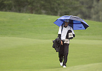 Middle Tennessee States Brad Simons walks towards the 9th hole with an umbrella as the rain started to pour at Gold Mountain during the first day of the NCAA Division I Regional tournament.