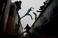 A devotee jump from a train to another heading home after the Akheri Munajat. Bishwa Ijtema (or Bishsho Istema the World or Global Congregation or Meeting) is an annual Tablighi Jamaat Islamic movement congregation held at Tongi, Bangladesh by the river Turag. It is the 2nd largest Muslim congregation in the world after the Hajj.  Dhaka, Bangladesh. Jan 11, 2015