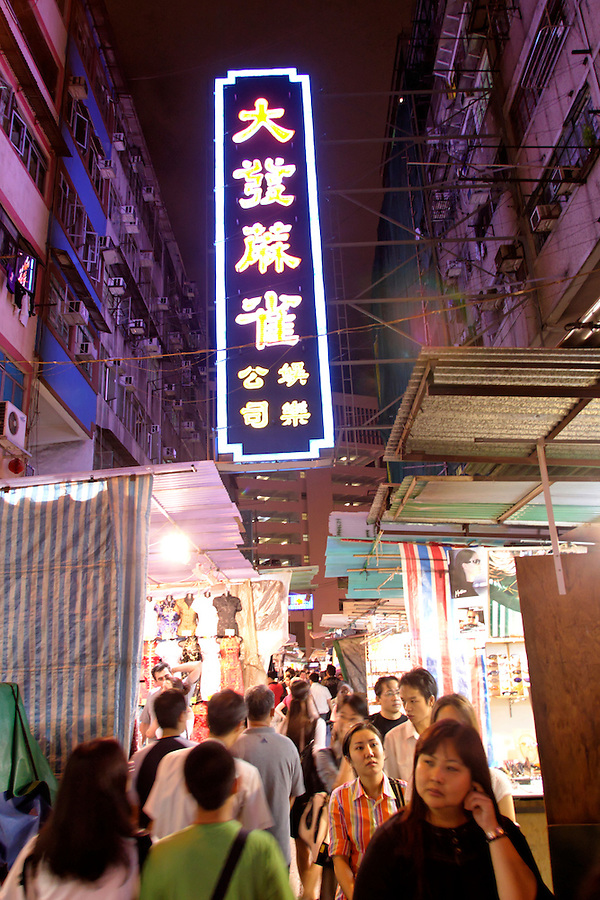 Neon mah jongg sign above crowd of shoppers at Temple Street Night Market, Kowloon, Hong Kong SAR, China, Asia