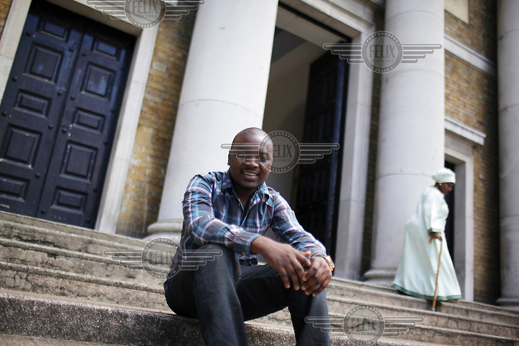 Ola Bamigboye sits on the steps of St Peter's Church in Walworth London. Ola is a law student living on the Aylesbury estate one of London's biggest and most deprived housing estates.