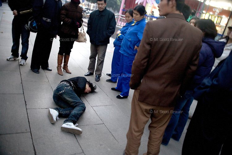 People surround a girl lying injured on the pavement in Nanjing, China.