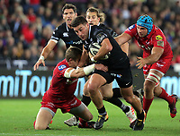 Kieron Fonotia of the Ospreys (C) is brought down by Hadleigh Parkes (L) and Tadhg Beirne of the Scarlets (R) during the Guinness PRO14 Round 6 match between Ospreys and Scarlets at The Liberty Stadium , Swansea, Wales, UK. Saturday 07 October 2017