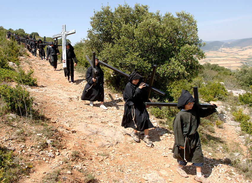 IRUNBERRI - LUMBIER, NAVARRE JUNE 11: Barefoot penitents dressed in black monks habits carry heavy crosses during the celebration of the 'Cruceros' brotherhood penitential pilgrimage to the 'Ermita de la Trinidad' on June 11, 2006 in Irunberri - Lumbier, Navarre. Photo by Ander Gillenea
