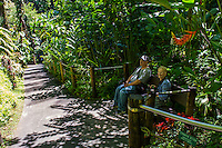 Tourists rest on a bench at Hawai'i Tropical Botanical Garden, Onomea, Big Island of Hawaiʻi.