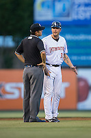 Kannapolis Intimidators manager Cole Armstrong (33) discusses a call with base umpire Mike Rains during the game against the Asheville Tourists at Intimidators Stadium on May 28, 2016 in Kannapolis, North Carolina.  The Intimidators defeated the Tourists 5-4 in 10 innings.  (Brian Westerholt/Four Seam Images)