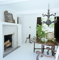In the dining room an ornate pewter chandelier is suspended above the antique gate-legged table and armchairs