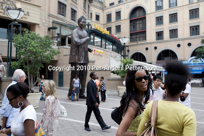 SANDTON,SOUTH AFRICA -JANUARY16:Upmarket people walk at Nelson MandelaSquareonJanuary16, 2010,in Johannesburg, South Africa. This is the most exclusive shopping mall in the country and some of the best hotels and restaurants in Johannesburg. A huge bronze statue of Nelson Mandela has been placed in the square. An ever increasing black middle class and elite has more money to spend that before and this is a popular place to buy famous brands.(Photo by Per-AndersPettersson/GettyImages)