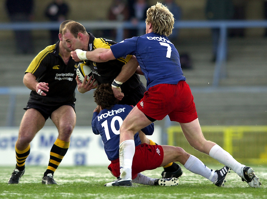 Photo. Richard Lane. .London Wasps v Stade Francais. Parker Pen Challenge Cup. 12/01/2003.Lawrence Dallaglio is tackled by Remy Martin and Diego Dominguez.