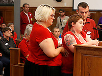 NWA Media/DAVID GOTTSCHALK - 8/19/14 - Laura Hampton, center, speaks with aid from Laura Phillips, left, and Nathan Sutherland Kordsmeier, right, all of Fayetteville, Tuesday August 19, 2014 during the public comment time of the Fayetteville City Council at the Fayetteville City Administration Building. The city council drew a large public turnout and response to a proposed anti-discrimination ordinance sponsored by Ward 2 Alderman Matthew Petty which would prohibit certain types of discrimination based on sexual orientation and gender identity and would create a municipal civil rights administrator position.