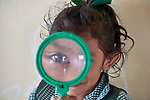 A girl uses a magnifying glass during class in Hiowa, Guyana.