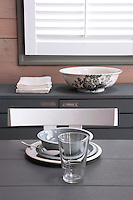 The grey and white decorative theme of the dining area is echoed in the crockery used for the place setting