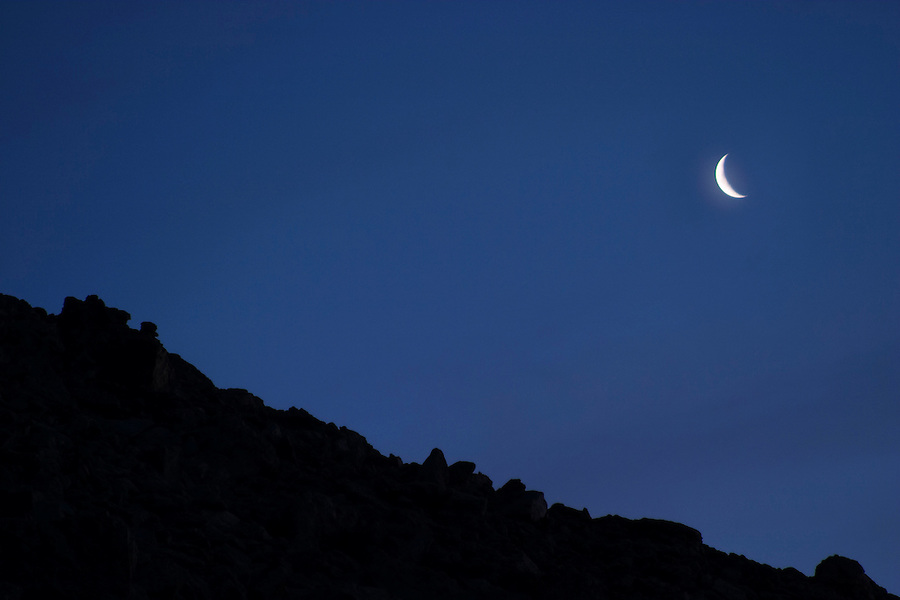 Crescent moon above silhouetted ridge line in clear night sky