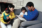 Palo Alto, Nuclear japanese family looking at book together, children eight months and two-years-old  MR