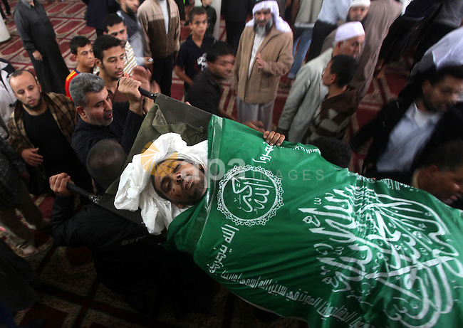Palestinians surround the bodies of a Hamas militant, who was killed in an Israeli air strike, during his funeral at a mosque in the central Gaza Strip November 17, 2012. Israeli aircraft bombed Hamas government buildings in Gaza on Saturday, including the prime minister's office, after Israel's cabinet authorised the mobilisation of up to 75,000 reservists, preparing for a possible ground invasion. Photo by Ashraf Amra
