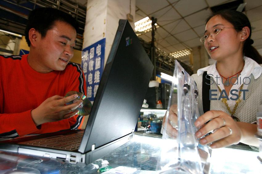 Li Daquan (gauche) et Qiang Yun (droite), mariés depuis trois ans, travaillent ensemble dans leur petit magasin d'informatique, à Shanghai, le 7 mai 2008. Li Daquan effectue des réparations et Qiang Yun vend toutes sortes de pièces détachées. Qiang Yun porte autour du cou un petit bouddha de jade offert par son père. « On n'est pas bouddhistes, mais le jade, ça porte bonheur », explique-t-elle. A l'annulaire gauche, on remarque une alliance surmontée d'un brillant. « C'est moi qui y tenais, raconte son époux. Car c'est un symbole occidental. » Photo par Lucas Schifres/Pictobank