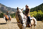 Young woman, teenager outdoors horseback riding on a crisp and cool fall morning amid aspen groves high in the Rocky Mountains, near Estes Park, Colorado, USA