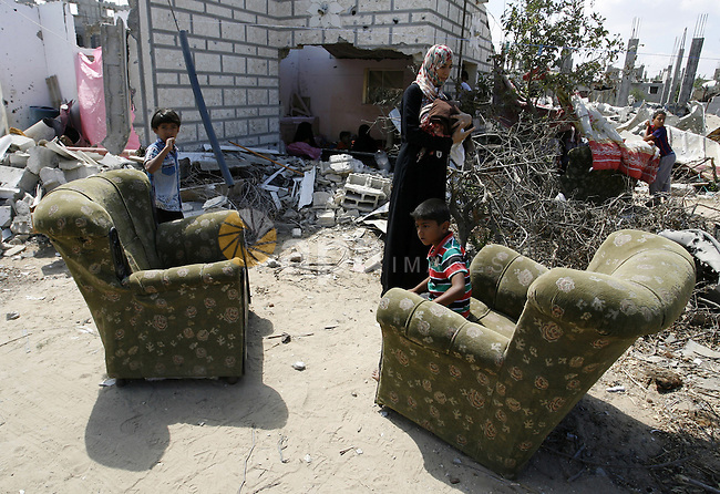 "A Palestinian woman works as her sons play at their destroyed house in Khan Yunis in the southern Gaza Strip on September 11, 2014. Israel's deputy foreign minister,Tzahi Hanegbi , warned that Hamas was likely to resume ""violence"" if it feels it has made no political gains from upcoming talks in Cairo. Photo by Abed Rahim Khatib"