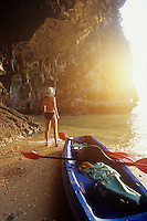 Young womanin bikini checks out the stalactites hanging from Sea Cave ceiling, Phra Nang Beach, Thailand