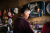 51 year old Goh Kuam Boon, a former pig farmer and a  survivor of the Nipah virus helps his wife in the kitchen of their house in Bukit Pelandok in Nageri Sembilan, Malaysia on October 16th, 2016. <br /> In September 1998, a virus among pig farmers (associated with a high mortality rate) was first reported in the state of Perak in Malaysia. Dr. Chua investigated and discovered the virus and it was later named, Nipah Virus. The outbreak in Malaysia was controlled through the culling of &gt;1 million pigs.