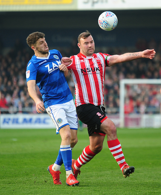 Macclesfield Town's James Pearson battles with Lincoln City's Matt Rhead<br /> <br /> Photographer Andrew Vaughan/CameraSport<br /> <br /> The EFL Sky Bet League Two - Lincoln City v Macclesfield Town - Saturday 30th March 2019 - Sincil Bank - Lincoln<br /> <br /> World Copyright © 2019 CameraSport. All rights reserved. 43 Linden Ave. Countesthorpe. Leicester. England. LE8 5PG - Tel: +44 (0) 116 277 4147 - admin@camerasport.com - www.camerasport.com