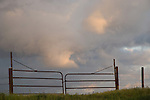 Metal gate panels silhouetted against a stormy sky at sun down, Parkfield Grade Road, Fresno Co., Calif.