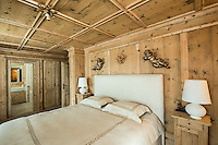 The traditional style wood panelled chalet's master bedroom with ensuite bathroom
