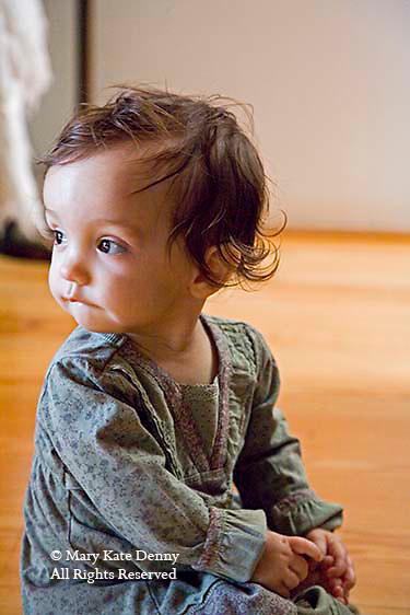One and a half year old brunette toddler girl sits on floor indoors and looks outdoors