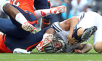 Brigham Young quarterback Taysom Hill (4) is tackled by Virginia  defender after a run during the first half of the game in Charlottesville, Va. Virginia defeated Brigham Young 19-16. Photo/Andrew Shurtleff